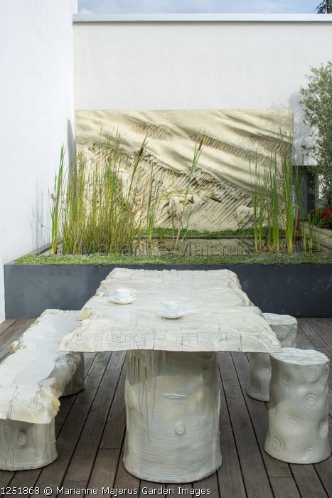 "Contemporary terrace, table, bench and stools designed by Gaetano Pesce, raised pond, ""La Tempesta"" (1981) wall art by Francesco Somaini"