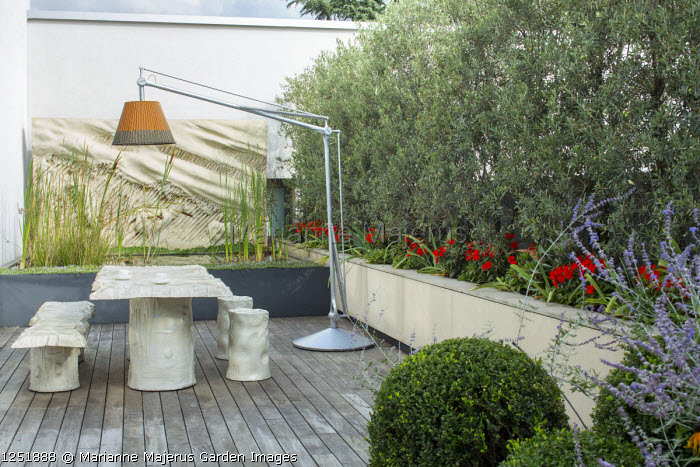 """Contemporary terrace, suspended lamp over table, benches and stools designed by Gaetano Pesce, raised pond, Olea europaea 'Cipressino' screen underplanted with Impatiens New Guinea Group, clipped box balls, """"La Tempesta"""" (1981) wall art by Francesco Somaini"""
