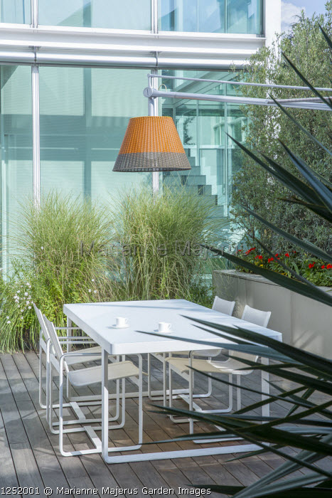 Contemporary table and chairs under suspended lamp on terrace, Miscanthus sinensis 'Morning Light'