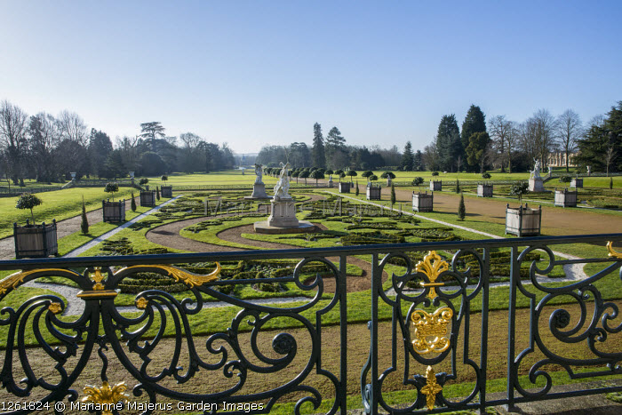 View from terrace over formal parterre garden, classical stone statues on plinths, iron railings