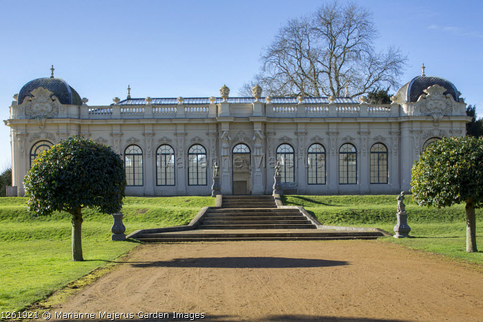 Wide path leading to Orangery, steps, statues on plinths