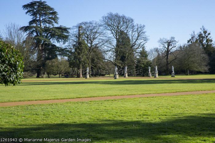 Path through lawn, view to statues on stone plinths