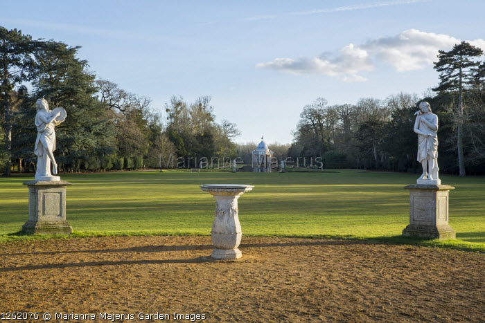 View across lawns to Archer Pavilion, classical statues on stone plinths