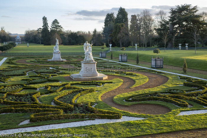View across formal parterre garden, classical stone statues on plinths, Versailles cases