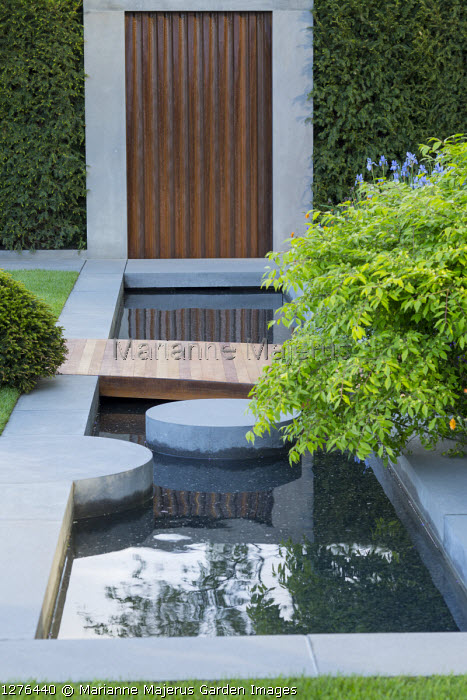 Formal pool, stepping stone, Geum 'Totally Tangerine', Euonymus alatus 'Compactus', clipped Taxus baccata mound, timber path across pond, Portland cement concrete
