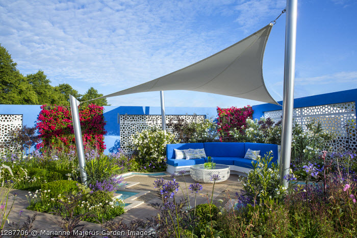 Sunsail over mediterranean-style garden, blue cushions on built-in bench, decking, white aluminium panels set in blue painted wall with living green Bougainvillea 'Barbara Karst' walls