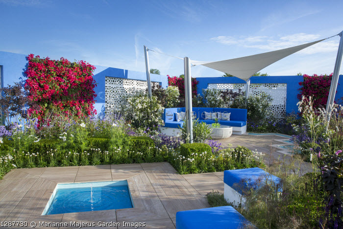 Sunsail over mediterranean-style garden, blue cushions on built-in bench and stools, square pond and fountain set in decking, white aluminium panels in blue painted wall with living green Bougainvillea 'Barbara Karst' walls, Armeria pseudarmeria 'Ballerina White' edging