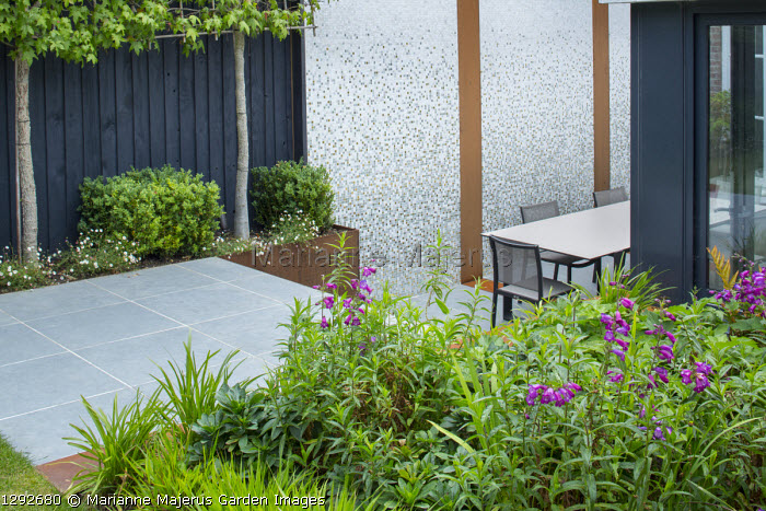 Penstemon 'Raven' in border, porcelain tile paving, table and chairs on patio, mosaic tiled wall with Cor-Ten steel