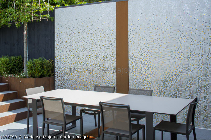 Table and chairs on sunny patio, mosaic tiled wall with Cor-Ten steel
