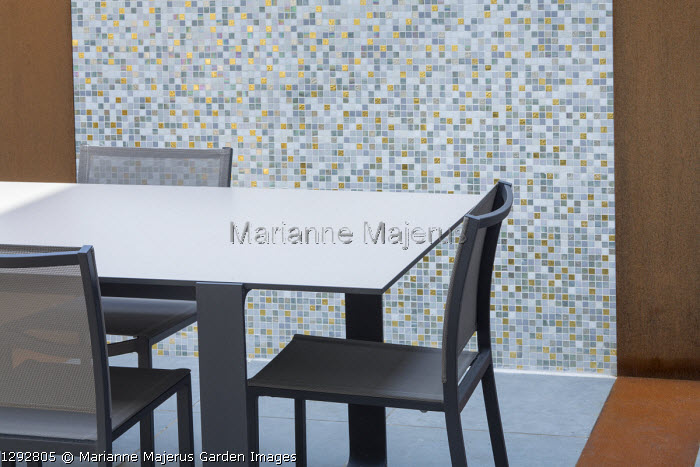 Table and chairs on patio, mosaic tiled wall with Cor-Ten steel