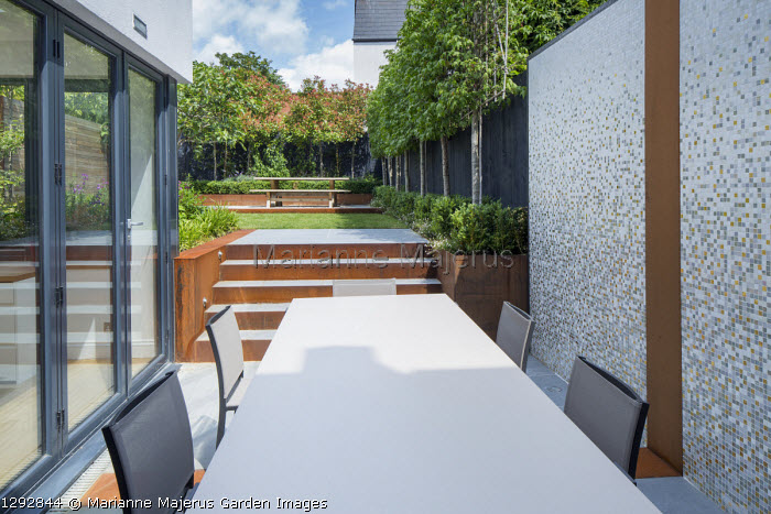 Contemporary table and chairs on patio by house, Cor-Ten steel steps leading to lawn, wooden table and benches on upper terrace, pleached Liquidambar styraciflua screen against black painted fence