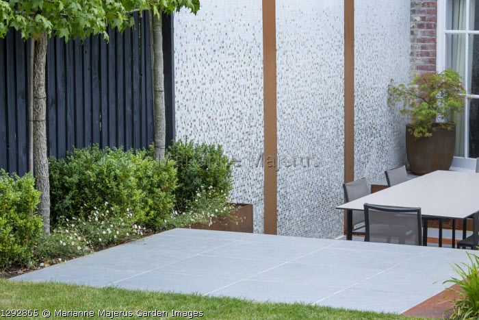 Table and chairs on patio by house, black painted fence underplanted with box cubes and Erigeron karvinskianus, mosaic tiled wall, acer in container, porcelain tile paving