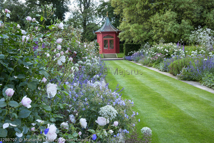 View along double perennial borders to red painted oriental summerhouse, lawn with stone mowing strips, roses, Geranium pratense 'Mrs Kendall Clark', Allium nigrum