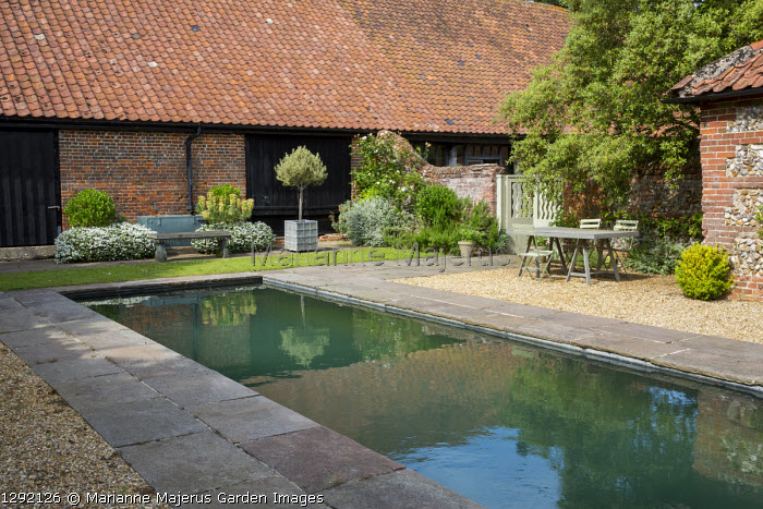 Formal pool with stone edging, table and chairs on gravel terrace