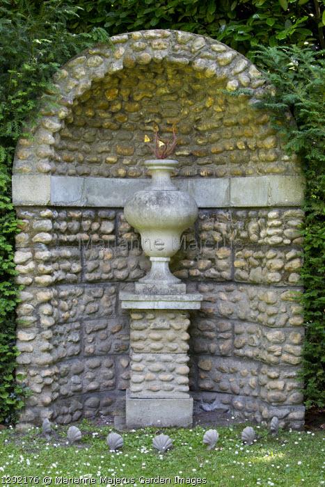 Stone urn on plinth in berceau