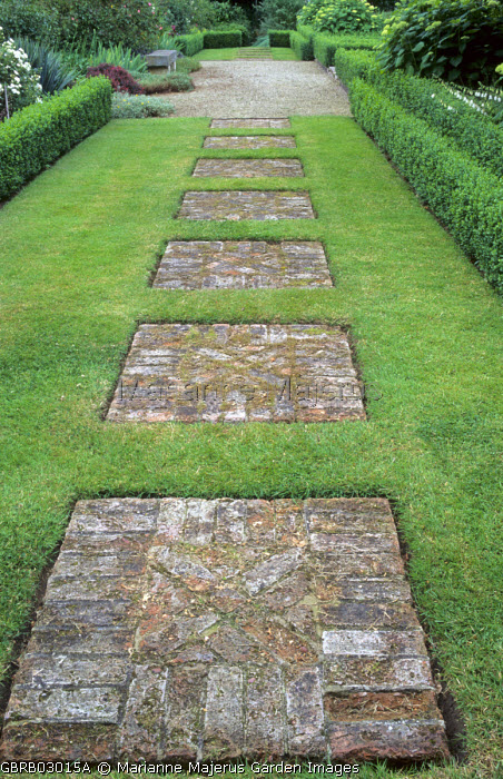 Stepping stone path of brick squares set in lawn, box-edged borders
