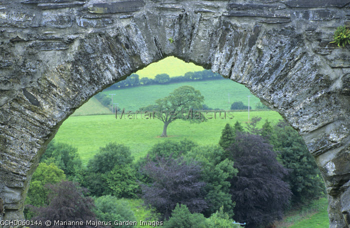 View under stone archway to fields, framed view, borrowed view
