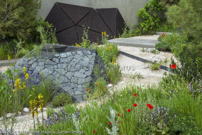 Black basalt stone raised pool, Asphodeline lutea, Papaver rhoeas, salvia