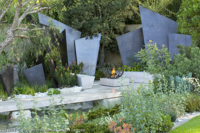 Fire bowl made from hammered bronze by James Price on limestone block, stone benches, Isoplexis canariensis, bronze-coated steel screens, limestone bridge over pond, Caesalpinia gilliesii, Schinus molle, Sphaeralcea incana
