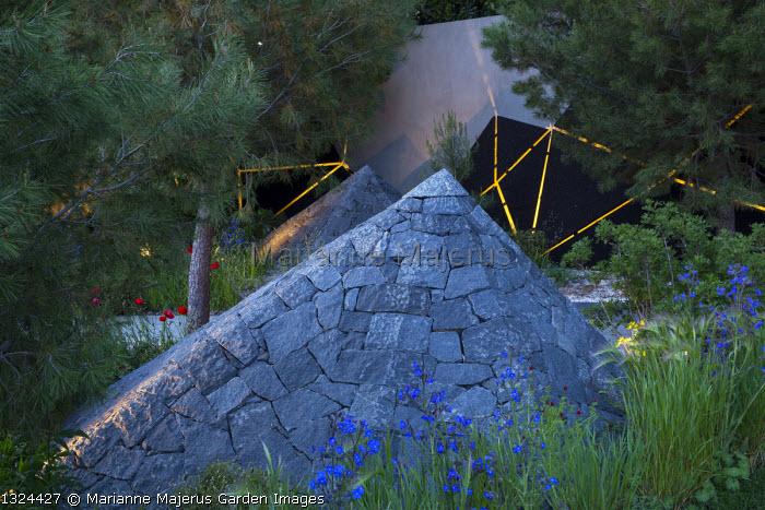 Black basalt stone pyramid at night, Anchusa azurea