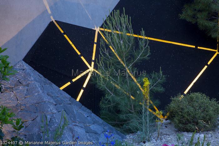 Black basalt stone pyramid, lit sculpture, Pinus halepensis