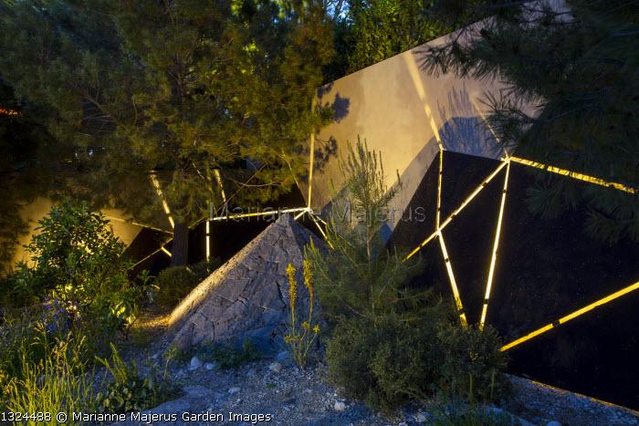 Pinus halepensis, lit sculptures against wall