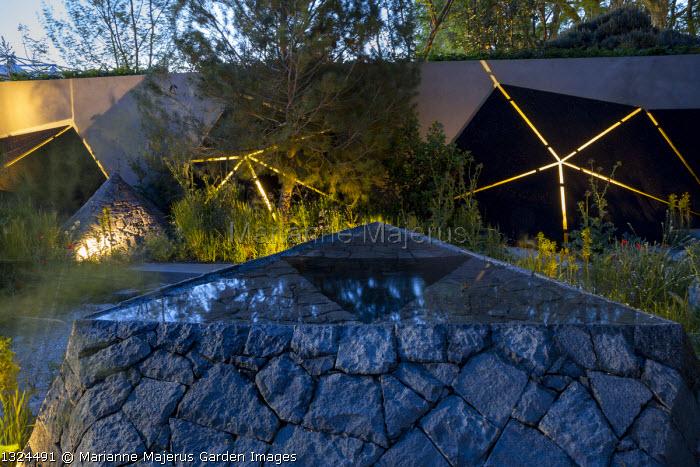 Black basalt stone raised pool, lit sculptures against wall