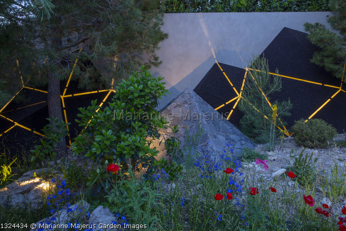 Black basalt stone pyramid, lit sculptures against wall, Anchusa azurea, Papaver rhoeas