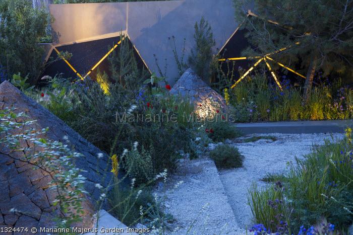 Mediterranean garden at night, lit sculptures against wall