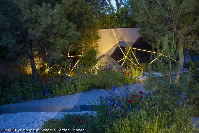 Mediterranean garden at night, lit sculptures against wall, Pinus halepensis, Anchusa azurea, Papaver rhoeas