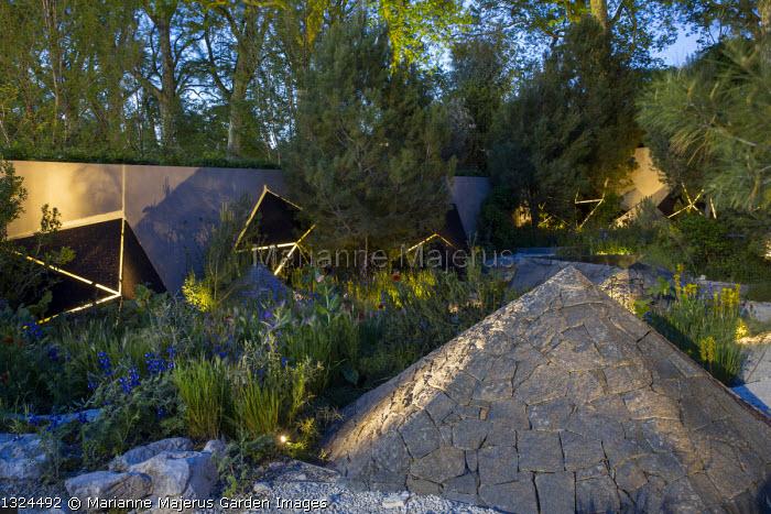 Black basalt stone pyramid, Pinus halepensis, lit sculptures against wall, Anchusa azurea