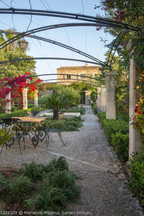 Table and chairs under pergola on mediterranean terrace, pebble paving, rosemary, bougainvillea