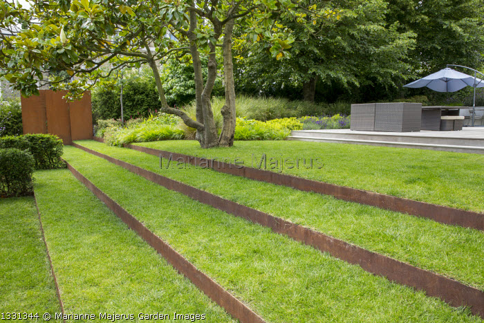 Grass steps with cor-ten steel risers under magnolia, cor-ten steel wall, contemporary furniture on terrace