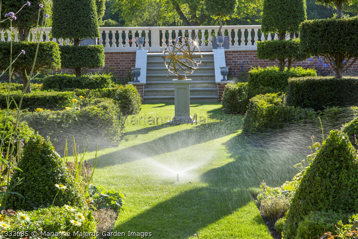 Irrigation on lawn, yew topiary, armillary sphere