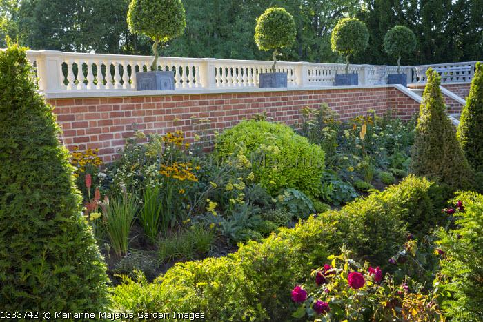 Balustraded brick wall, yew hedge, Achillea 'Moonshine', Helenium 'Wyndley', roses