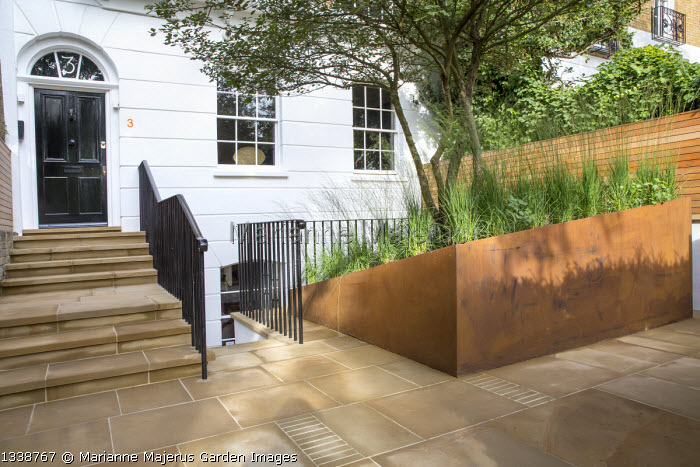 Molinia caerulea subsp. caerulea 'Heidebraut' in cor-ten steel raised bed in front garden, multi-stemmed Crataegus persimilis 'Prunifolia', stone paving, wooden fence, steps to front door