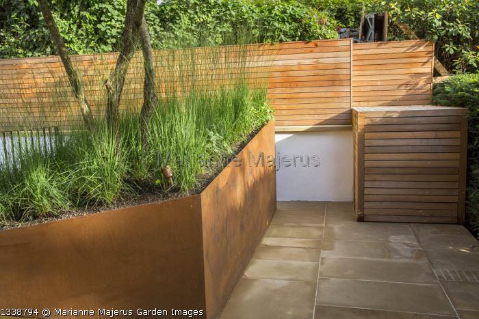 Molinia caerulea subsp. caerulea 'Heidebraut' in cor-ten steel raised bed in front garden, multi-stemmed Crataegus persimilis 'Prunifolia', stone paving, wooden fence and bin storage