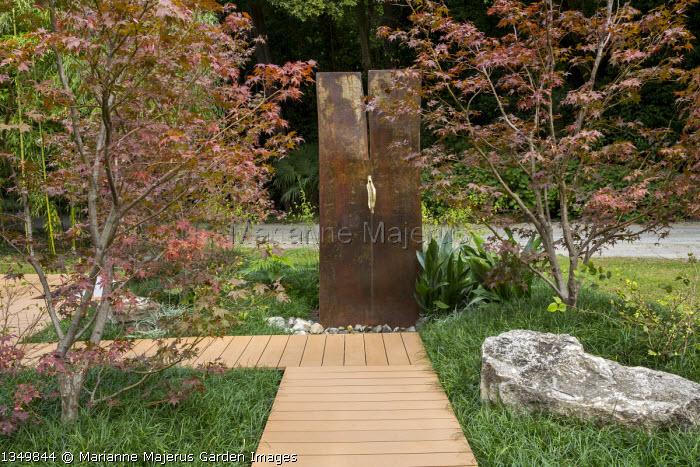 Water wall fountain, timber boardwalk path through carpet of Ophiopogon japonicus 'Gyoku-ryu', Acer palmatum