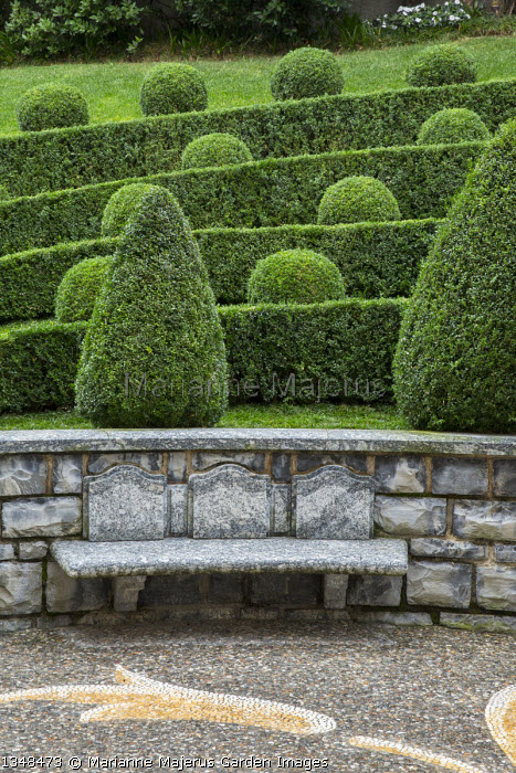 Box topiary on sloping bank, pebble mosaic paving, built-in stone bench