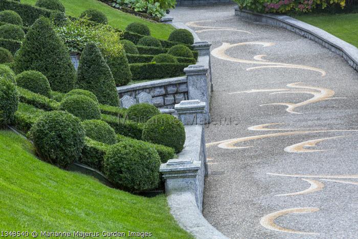 Box topiary on sloping bank, pebble mosaic paving, driveway