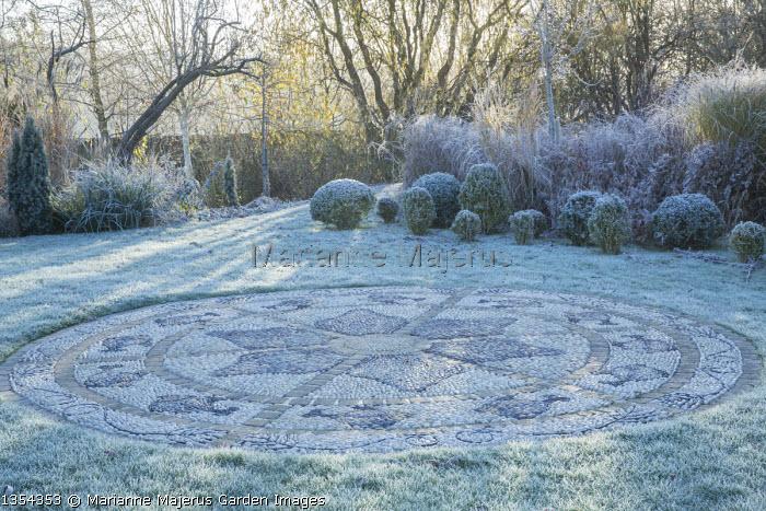 Circular pebble mosaic patio in frosty lawn, box balls