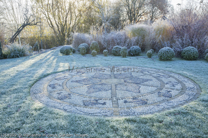 Circular pebble mosaic patio in frosty lawn, box balls