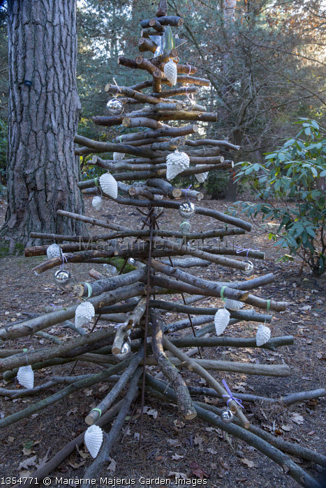 Christmas tree made from logs in woodland, pine cone and bauble decorations