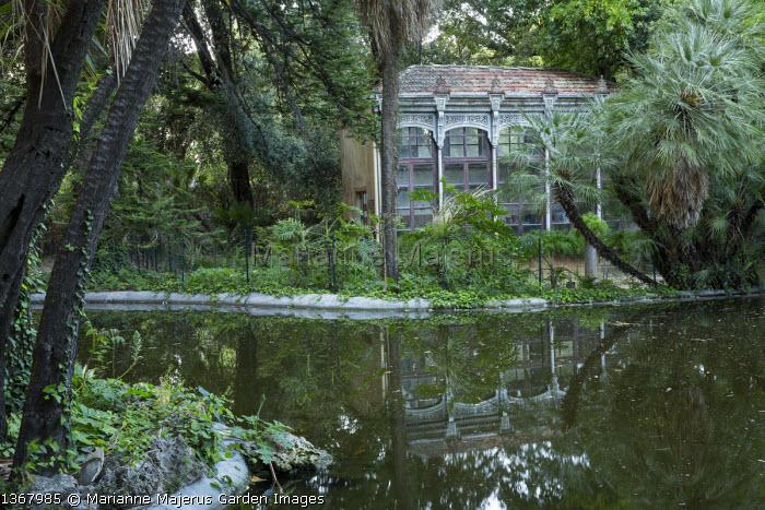 View across reflective pool to orangery in shady mediterranean garden