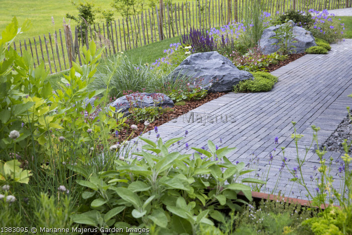 Stone paving, large rocks in border, salvia, herbs in raised bed, sage, lovage, chives