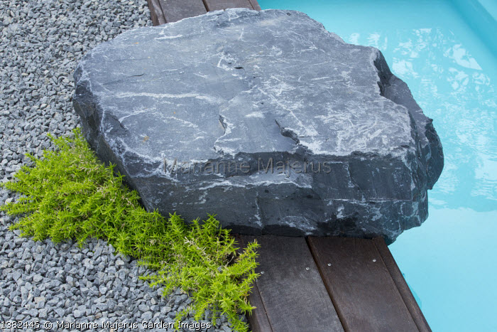 Large rock by timber-edged swimming pool, gravel