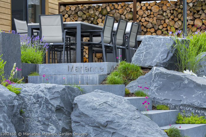 Stone steps leading to table and chairs on terrace, large rocks, cut log screen