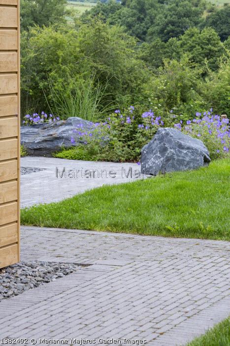 Stone path around house, large rocks, geraniums