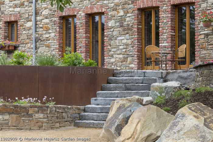 Chives and rosemary in Cor-Ten steel raised bed, stone steps leading to chairs on patio by house