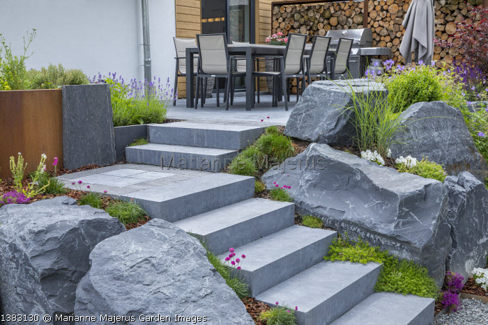 Stone steps leading to table and chairs on patio, rockery, large rocks
